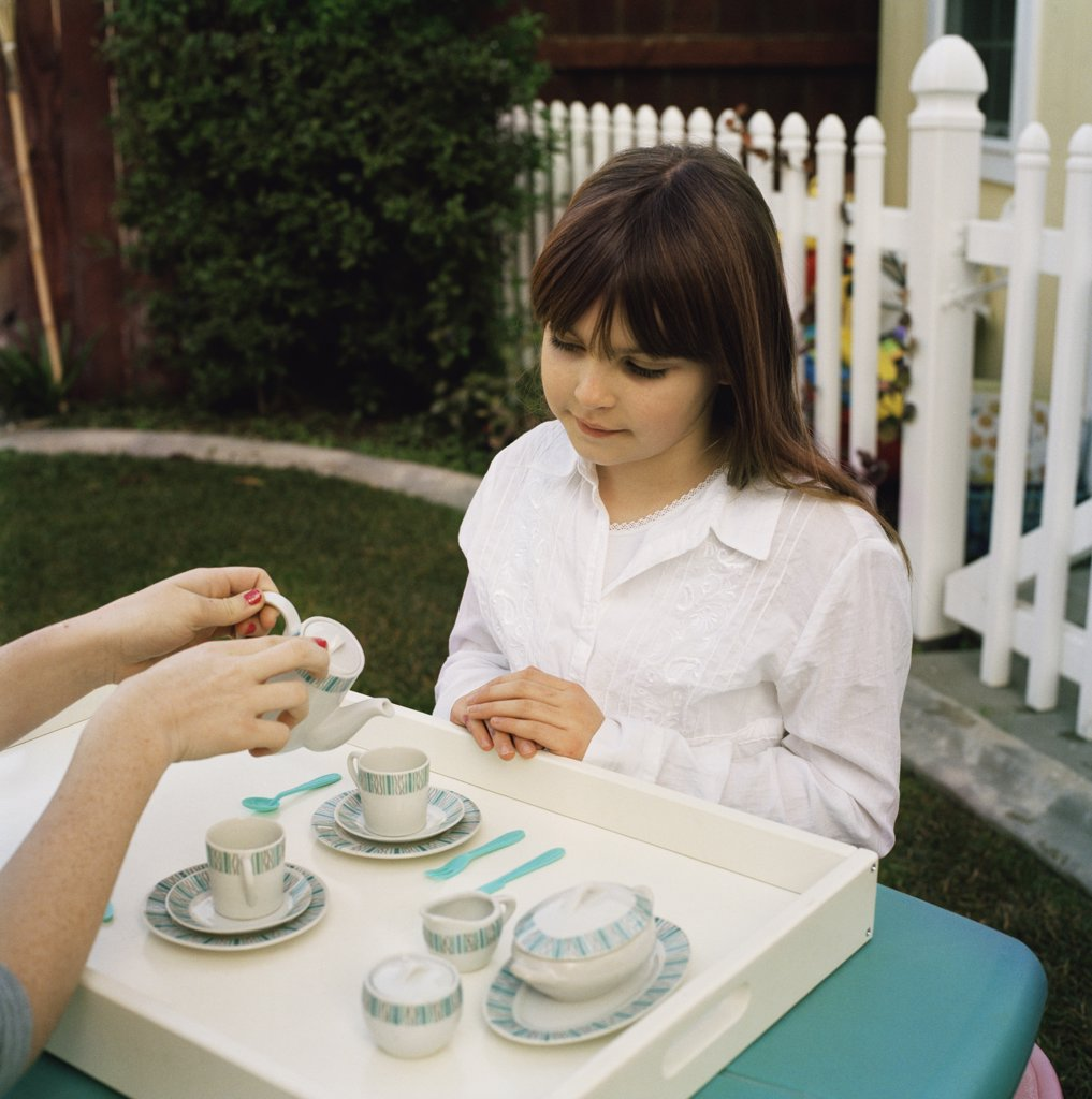 Children having a tea party in the garden : Stock Photo