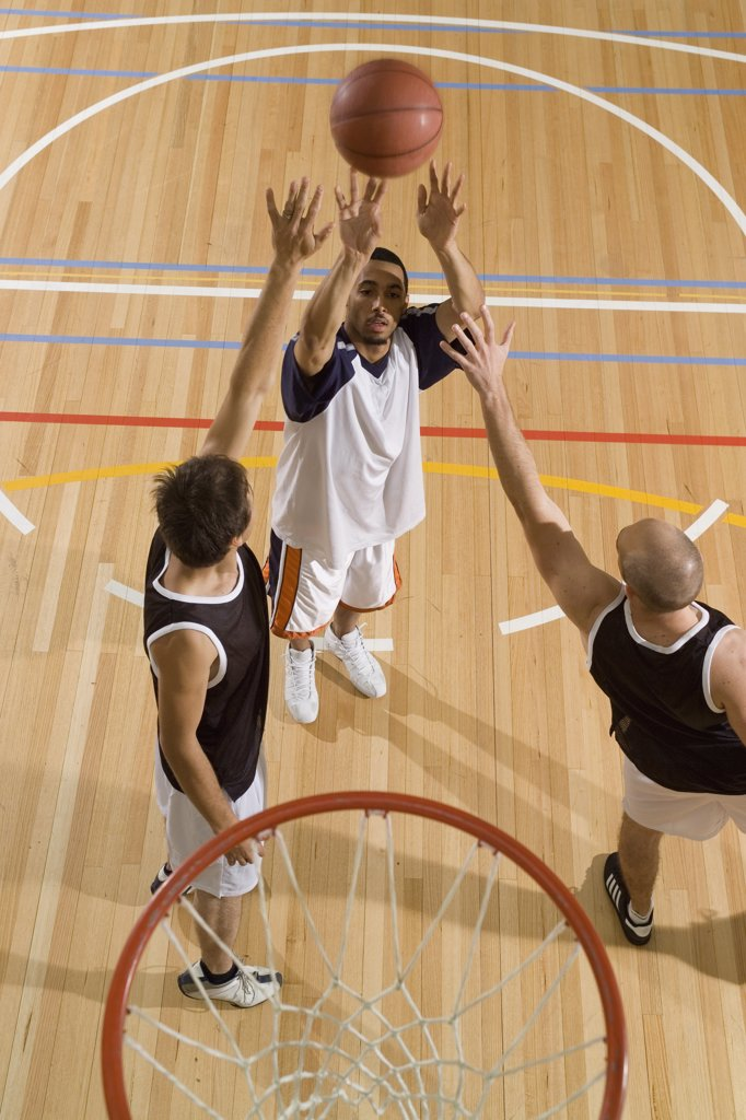One basketball player shoots the basketball while two more players try to block his shot : Stock Photo