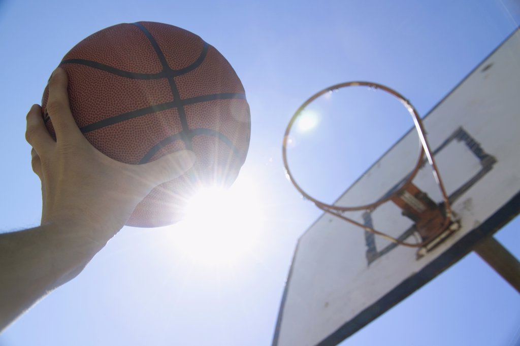 A human hand reaching up towards the sun and basketball hoop with holding basketball : Stock Photo