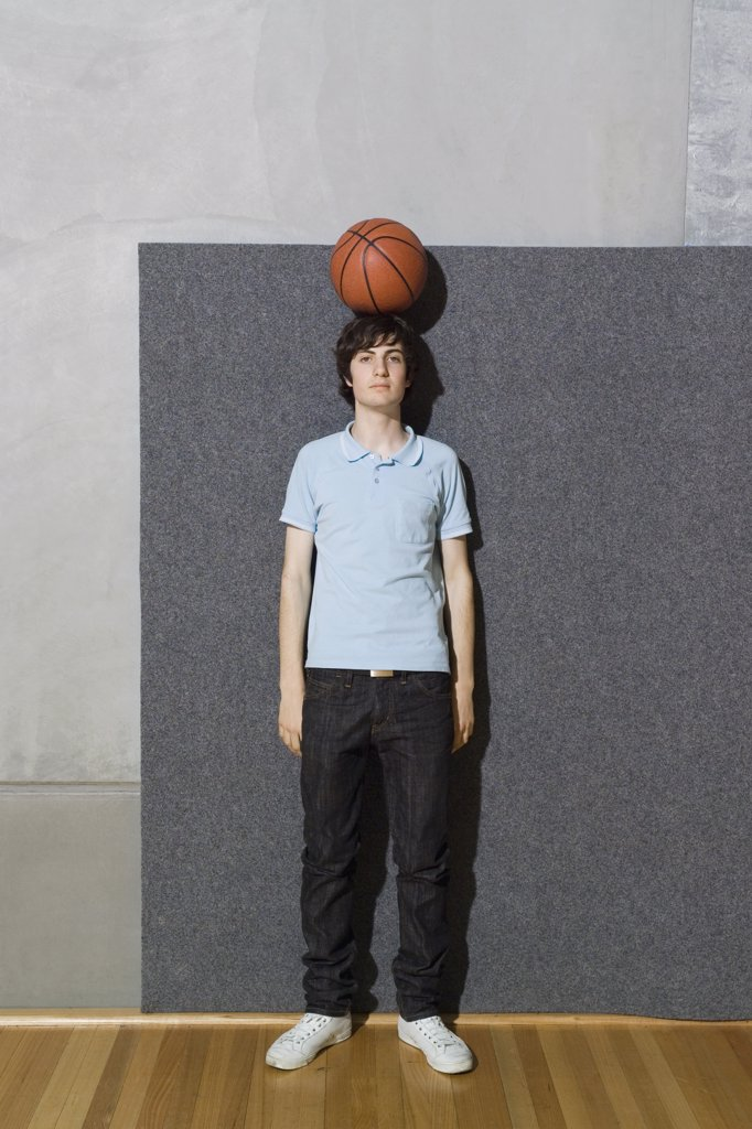 A young man standing with a basketball balanced on his head : Stock Photo