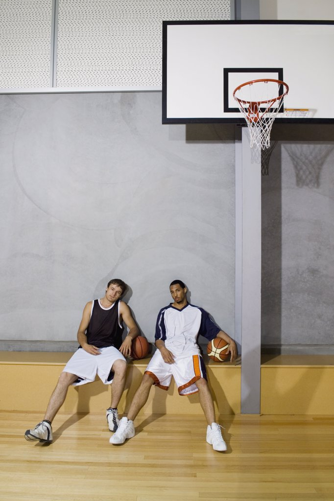 Two young men sitting on a bench at a basketball court : Stock Photo