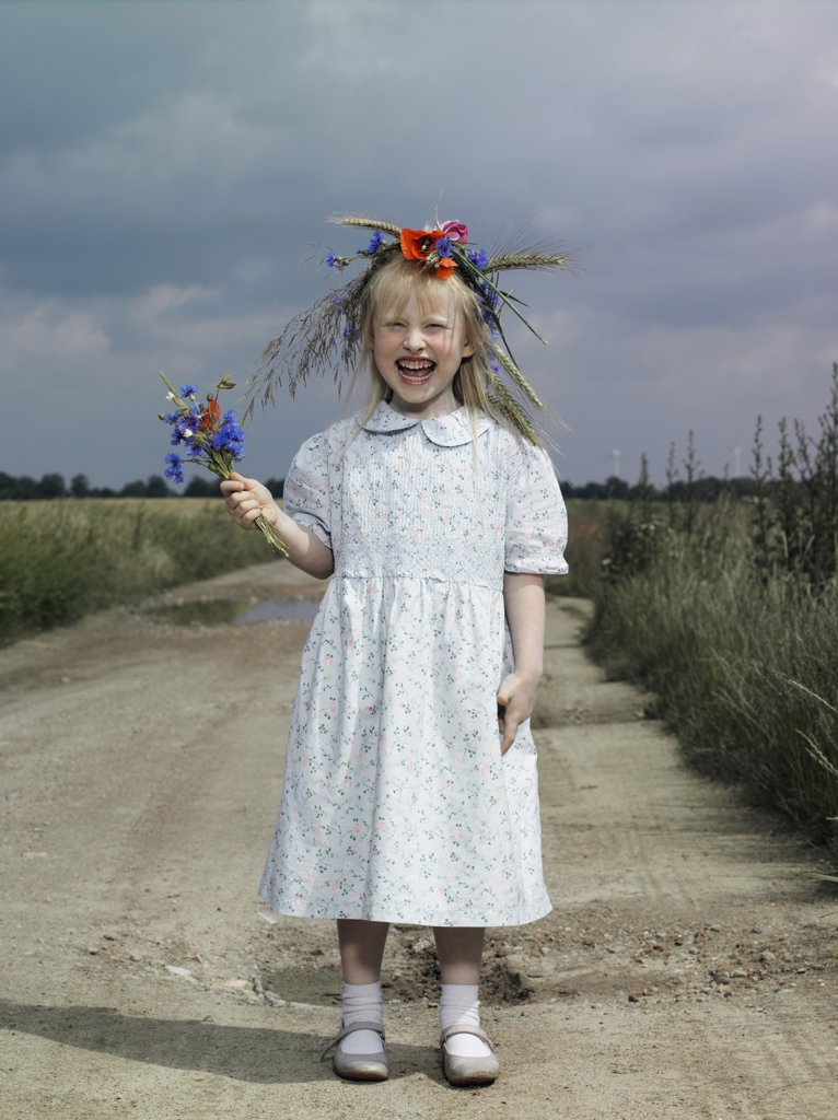 Stock Photo: 1570R-121900 A girl standing on a country road and holding wildflowers