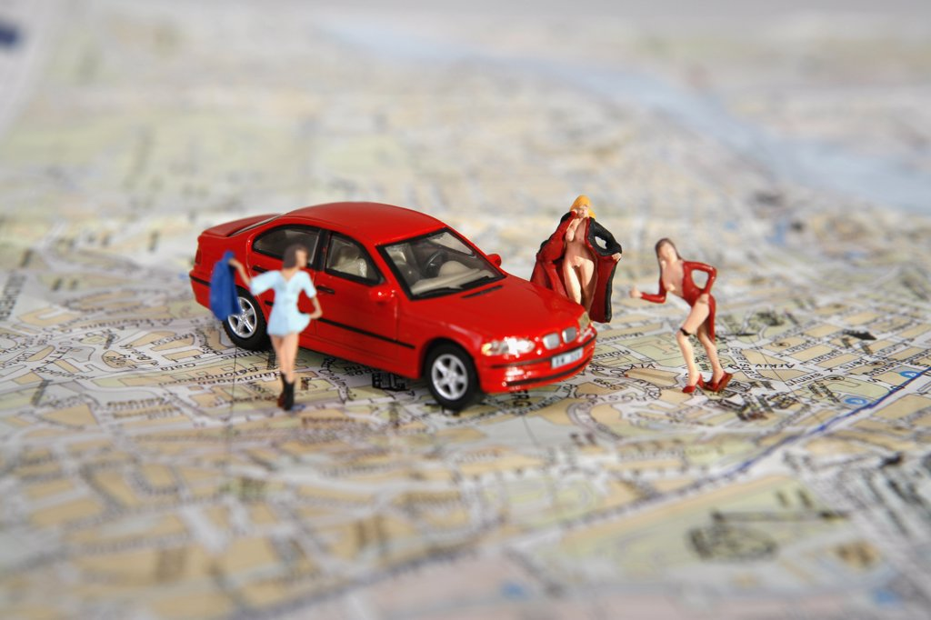 Women of the night figurines posed around a toy car on top of a road map : Stock Photo
