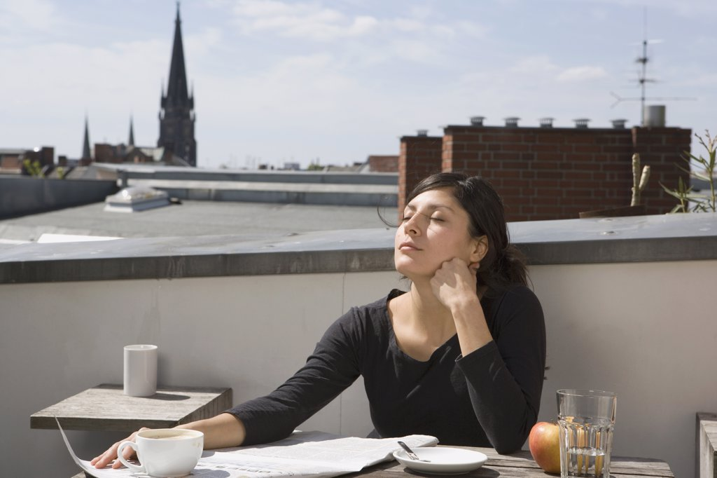 Woman sitting on a rooftop in the sun : Stock Photo