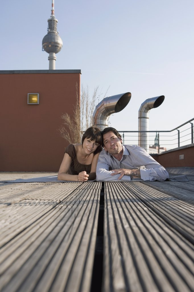 Portrait of a man and a woman lying together on a rooftop terrace : Stock Photo