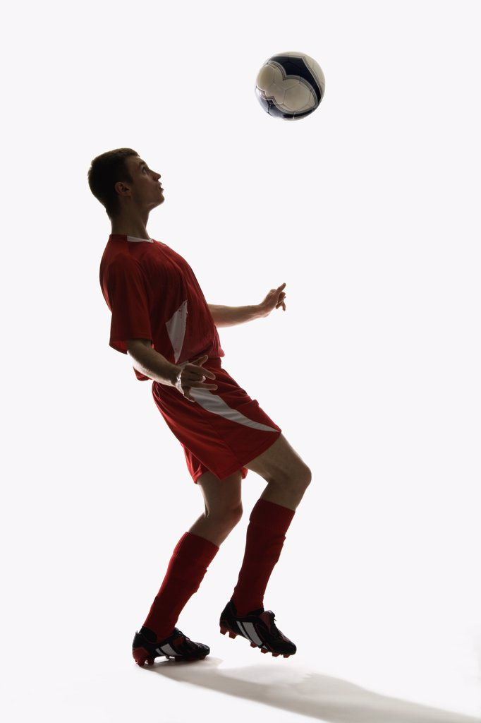 Stock Photo: 1570R-122448 Studio shot of a soccer player bouncing a soccer ball on his chest