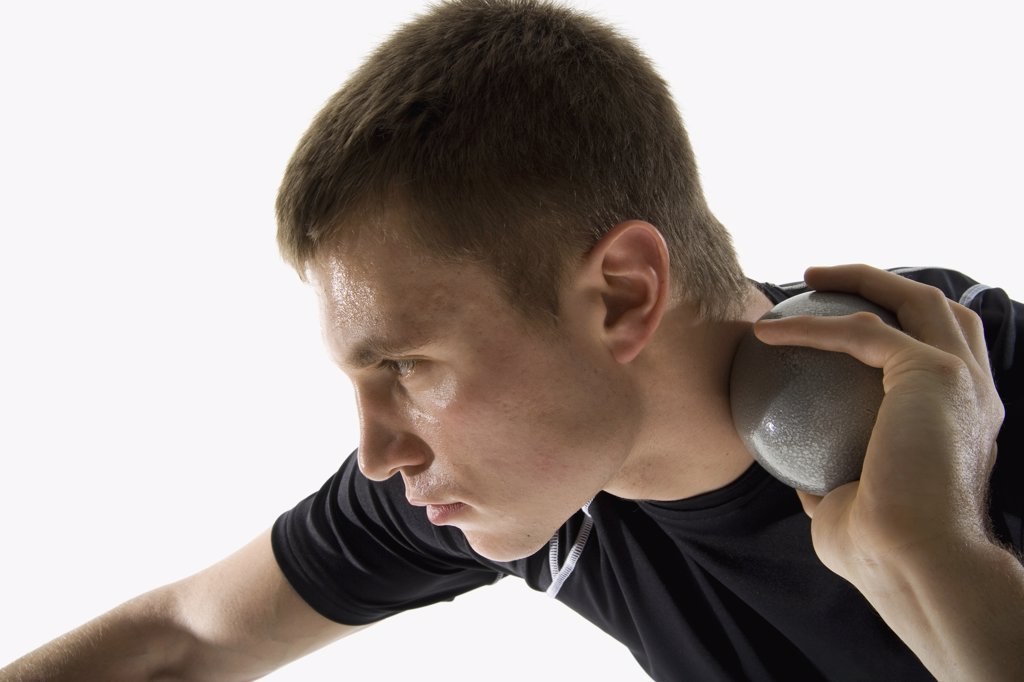 Stock Photo: 1570R-122470 Studio shot of a male track and field athlete holding a shot put ball