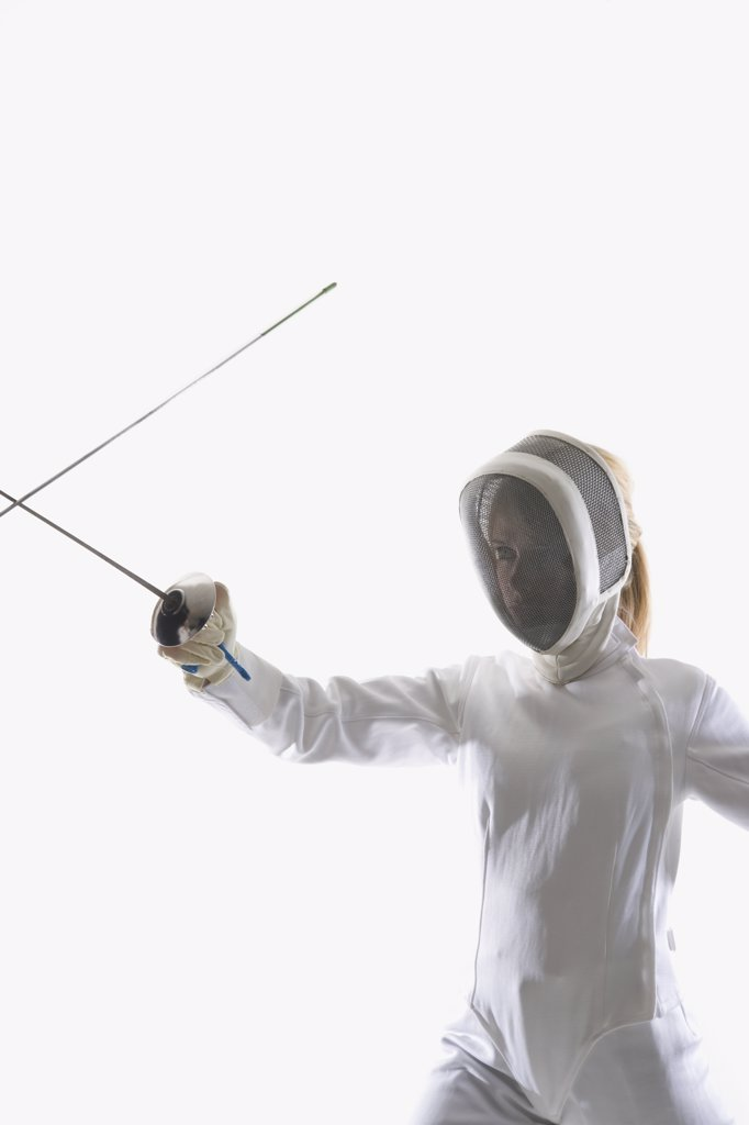 Stock Photo: 1570R-122500 Studio shot of female fencer posing with a fencing foil in a confrontation with another fencing foil