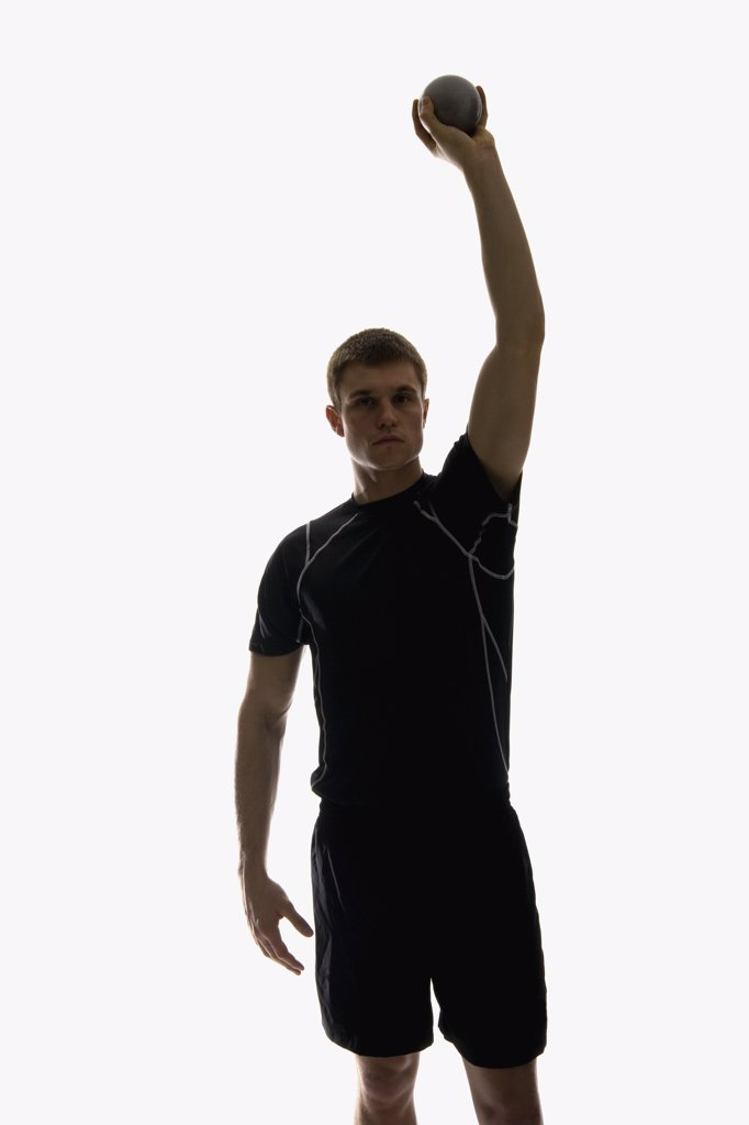 Stock Photo: 1570R-122501 Studio shot of a male track and field athlete holding a shot put ball