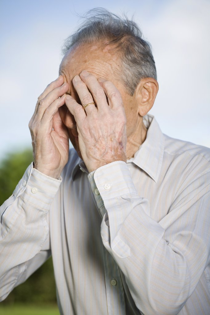 Stock Photo: 1570R-122576 A senior man covering his face with his hands