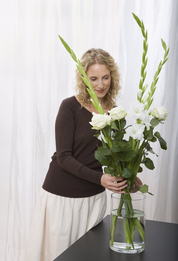 Stock Photo: 1570R-122901 A woman arranging a bouquet of sword lilies and roses
