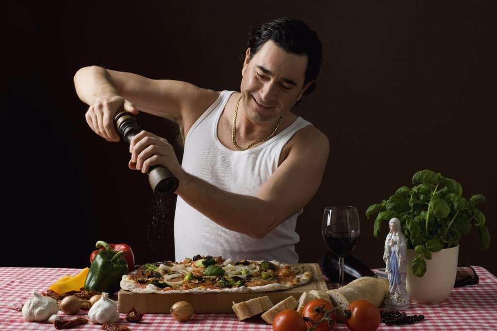 Stereotypical Italian man using a pepper mill on his pizza : Stock Photo