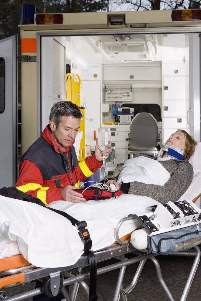 A paramedic assisting a woman in front of an ambulance : Stock Photo