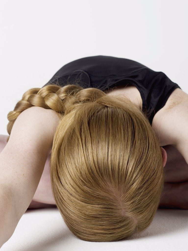 A young woman bending over and resting her head on the floor : Stock Photo