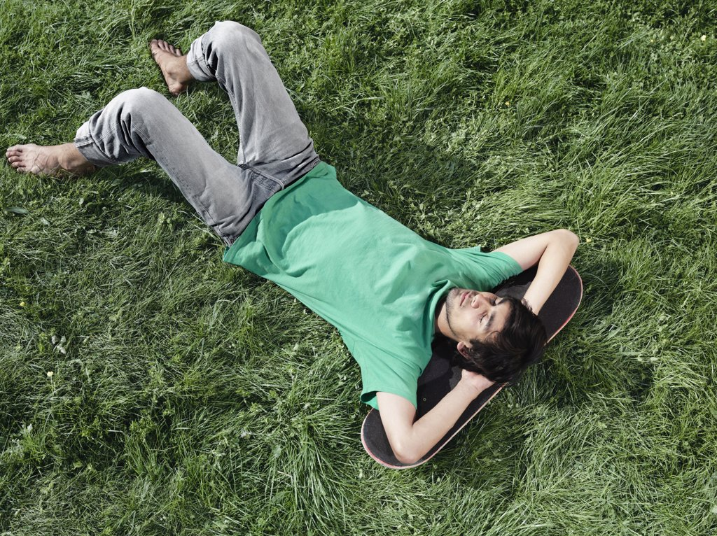 A young man lying in the grass with his head on a skateboard : Stock Photo