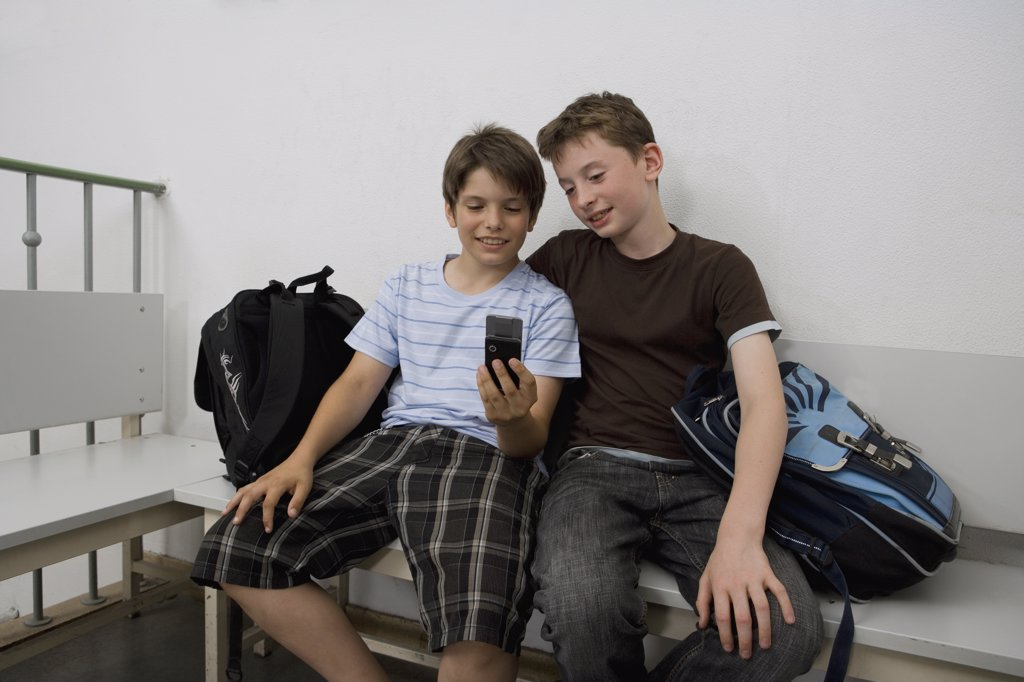 Two pre-adolescent boys sitting on a bench looking at a mobile phone : Stock Photo