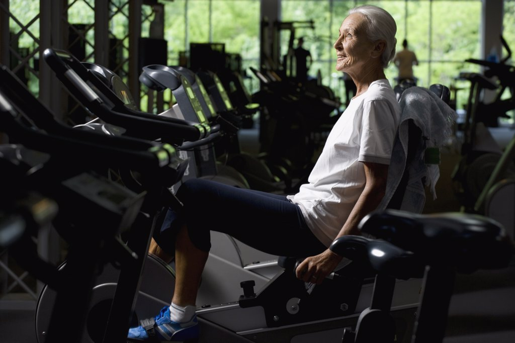 A senior woman on a stationary bike : Stock Photo
