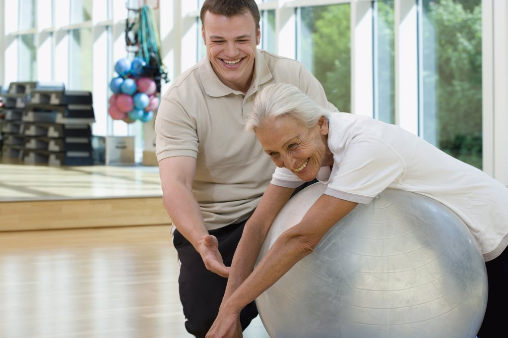 A senior woman on an exercise ball working with a trainer : Stock Photo