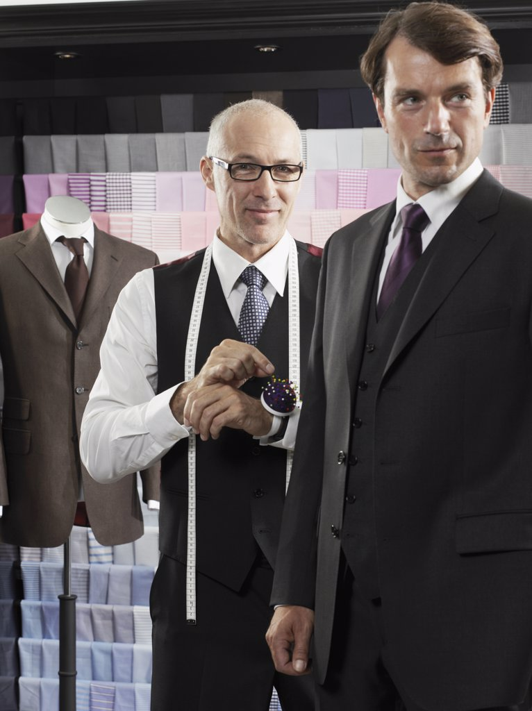 A tailor fitting a man with a suit : Stock Photo