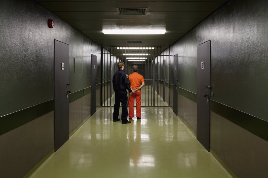 A prison guard leading a prisoner along a corridor : Stock Photo