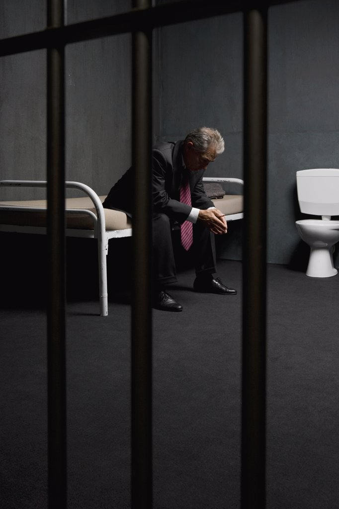 A businessman sitting on a bed in a prison cell : Stock Photo