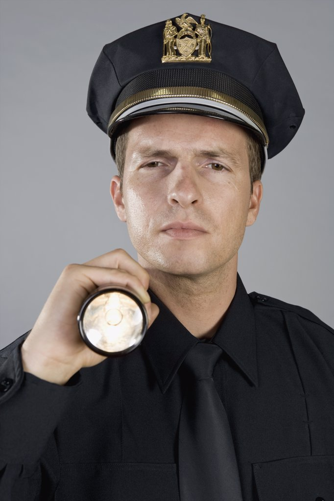 Portrait of a police officer holding a torch : Stock Photo