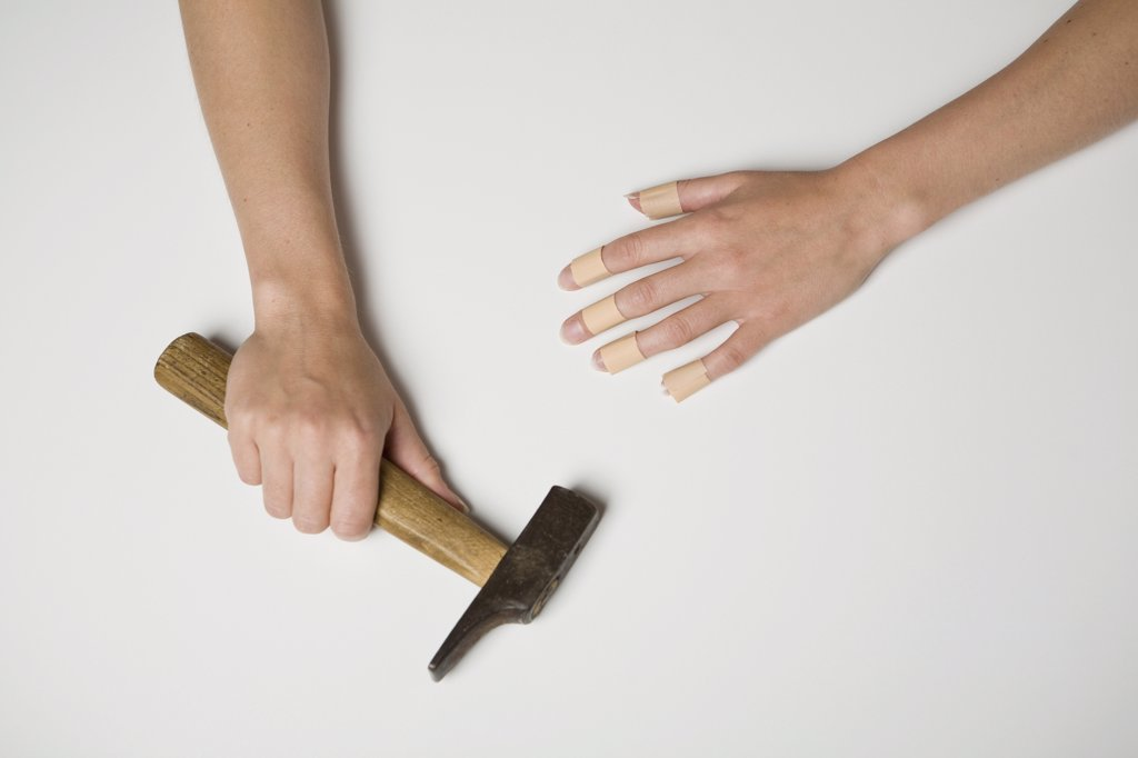 Stock Photo: 1570R-125169 A young woman with plasters on all fingers of one hand and in the other hand is a hammer