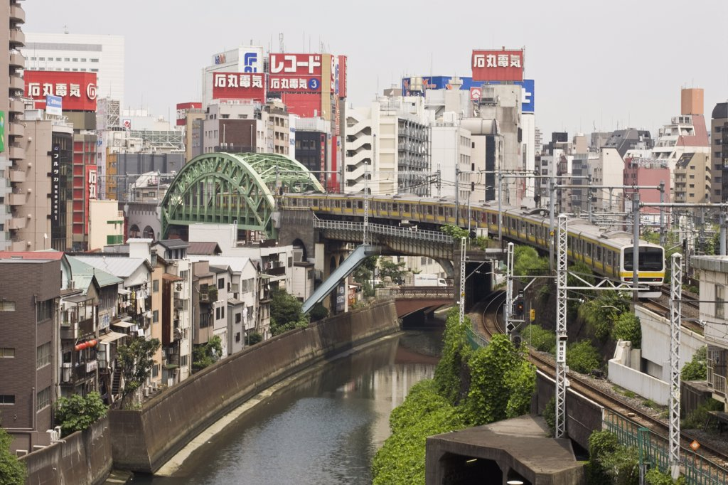 Train crossing the Kanda River with Akihabara district in background, Tokyo : Stock Photo