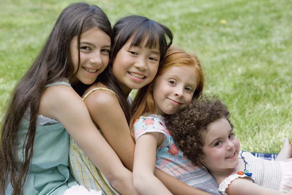 Four girls leaning on each other : Stock Photo