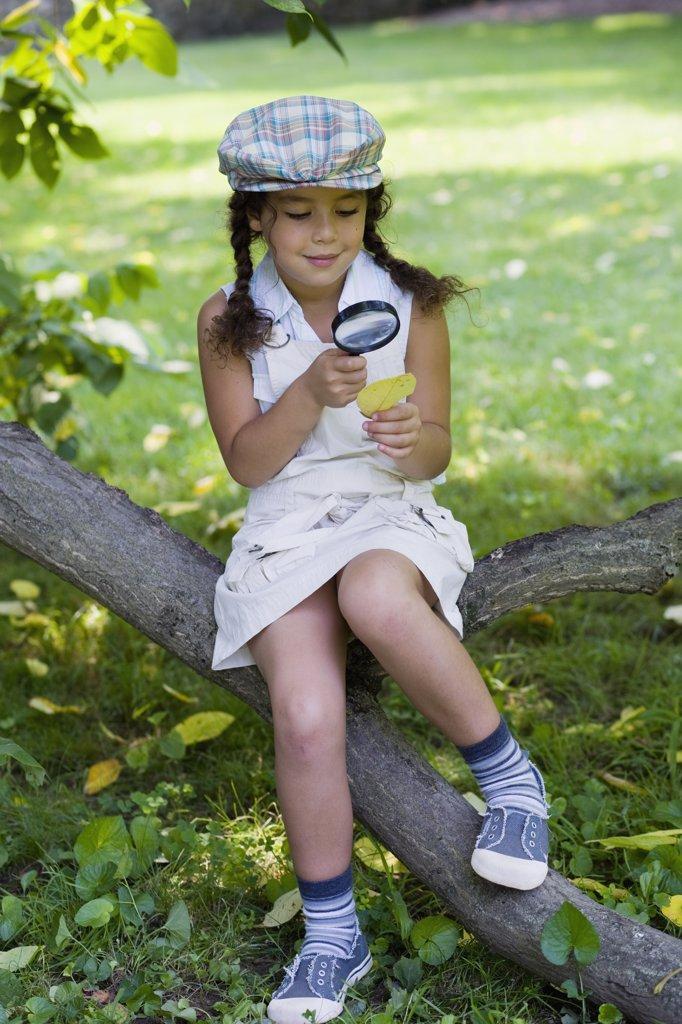 A girl sitting on a tree branch and looking at a leaf with a magnifying glass : Stock Photo