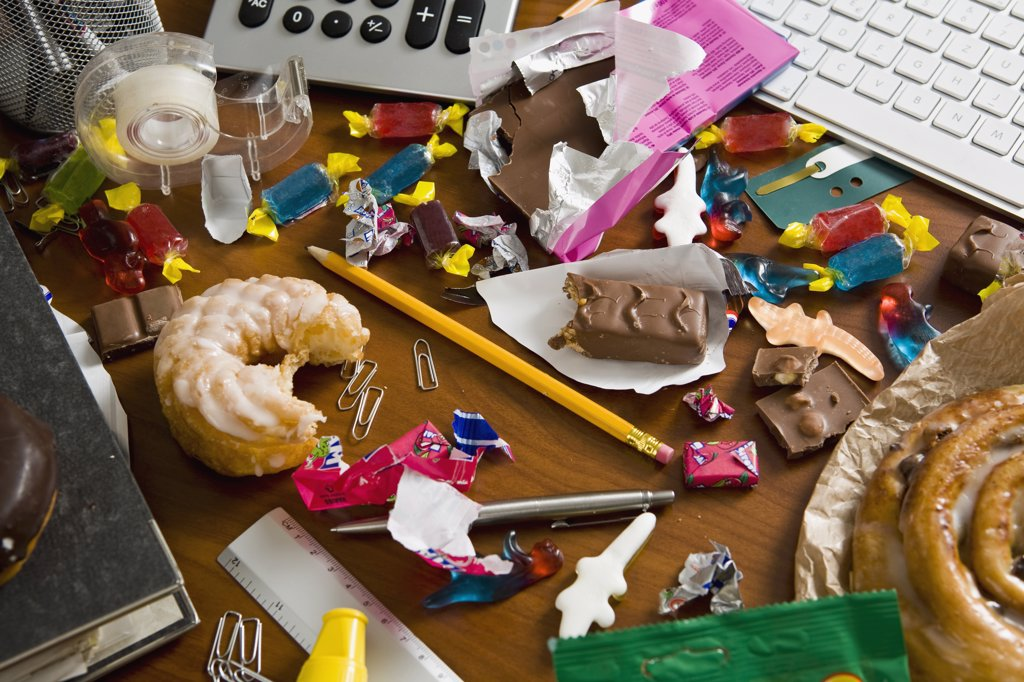 An office desk cluttered with candy and sweets : Stock Photo