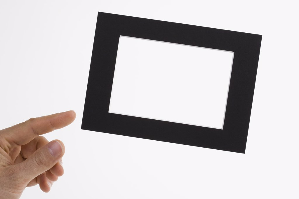 A human hand adjusting a slanted picture frame : Stock Photo