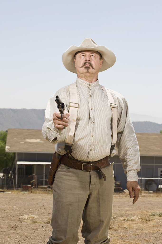 Portrait of a cowboy aiming his gun : Stock Photo