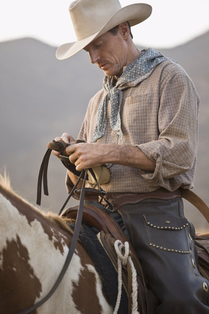 A cowboy sitting on his horse : Stock Photo