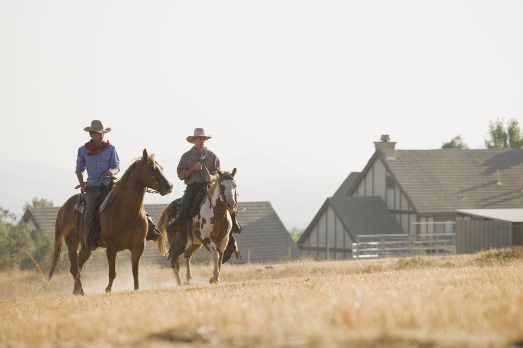 Stock Photo: 1570R-126020 Two cowboys riding horses through a field