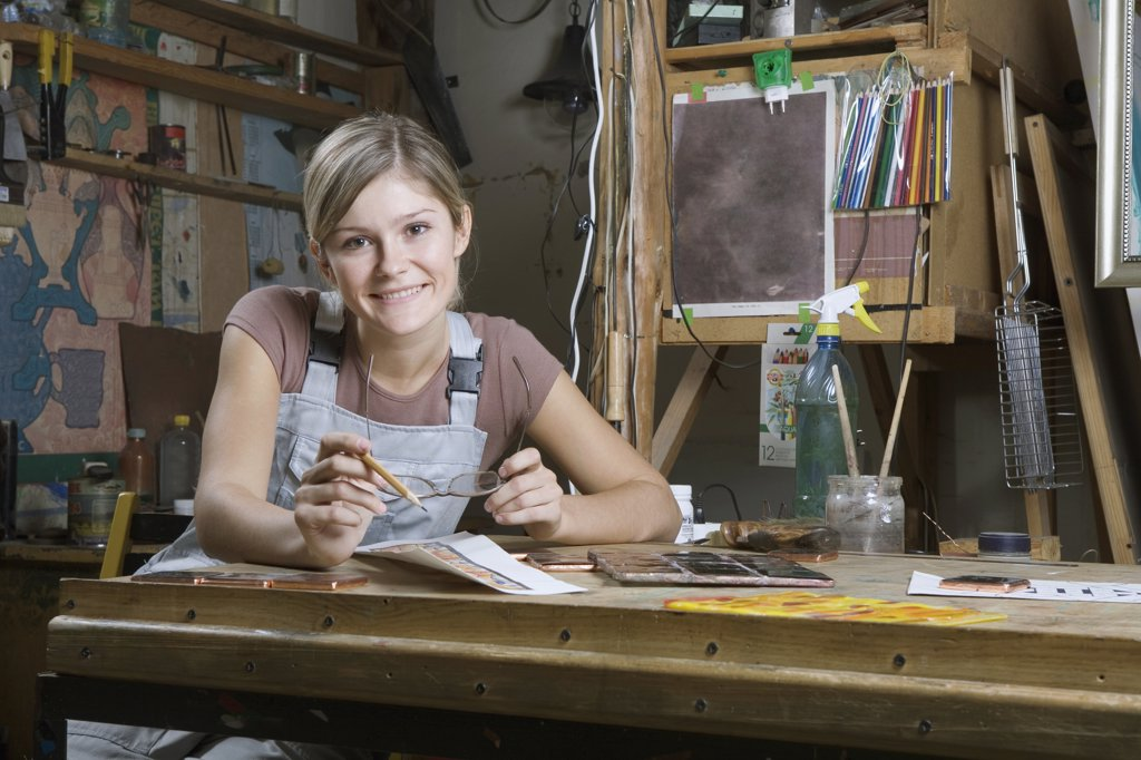 A young woman working in an art studio, portrait : Stock Photo