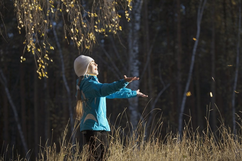 A young girl in a field catching leaves : Stock Photo