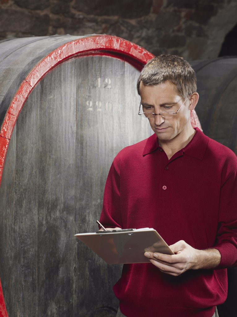 A vintner writing on a clipboard : Stock Photo
