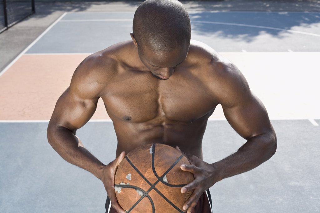 A basketball player holding a ball, portrait : Stock Photo
