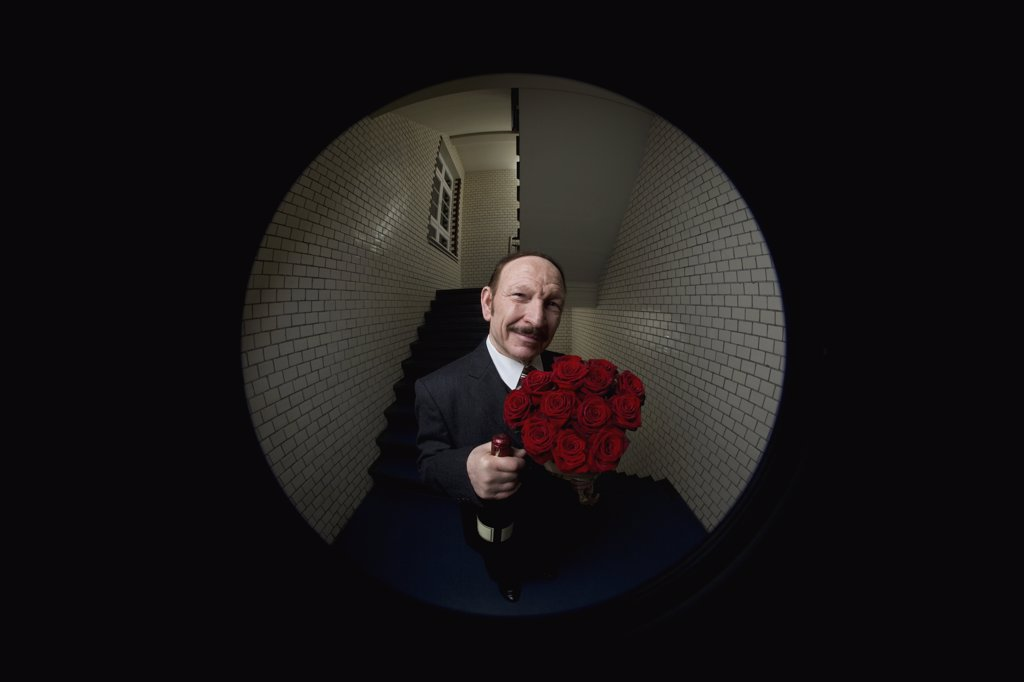Stock Photo: 1570R-126352 A man with roses and champagne viewed through a peephole