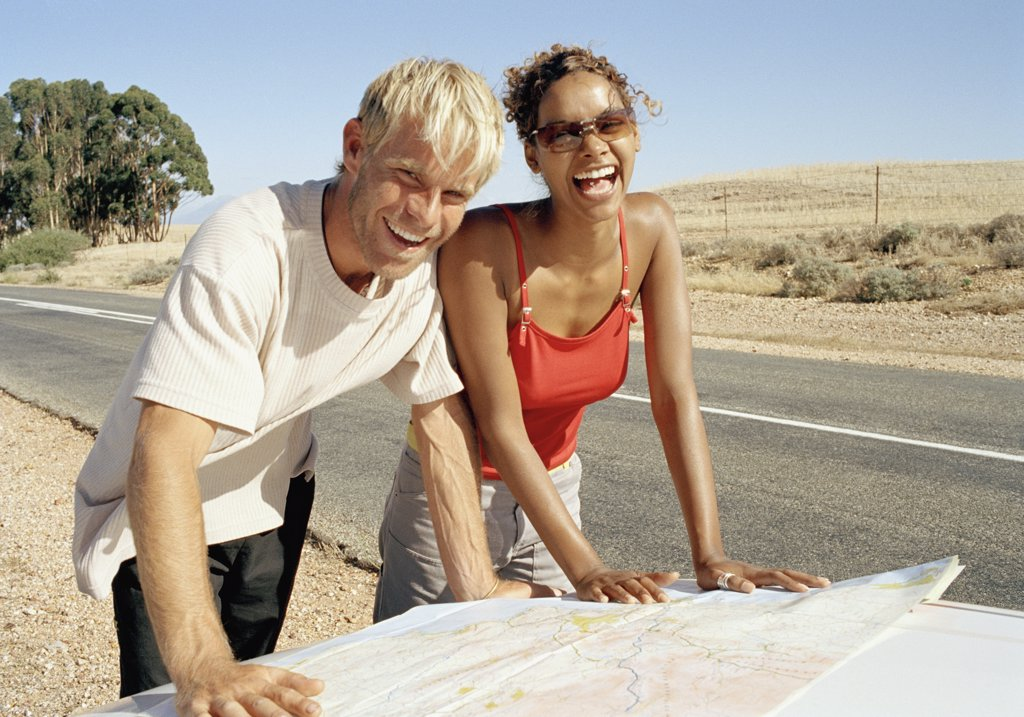 A man and a woman leaning on a car bonnet and reading a map : Stock Photo
