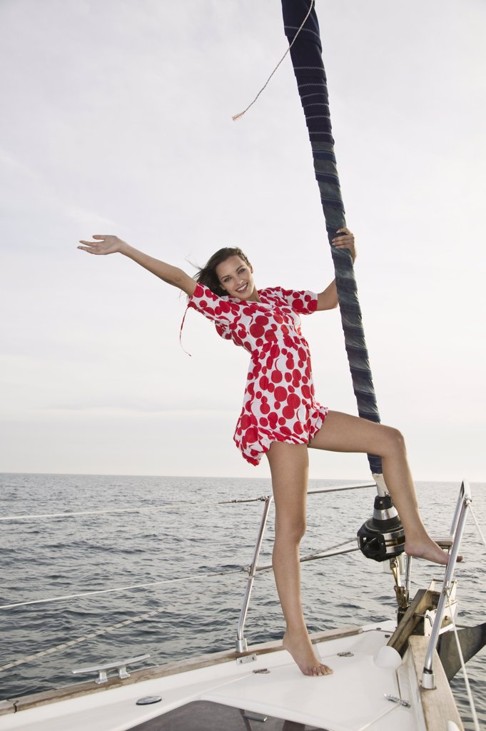 A woman standing on a yacht and waving : Stock Photo