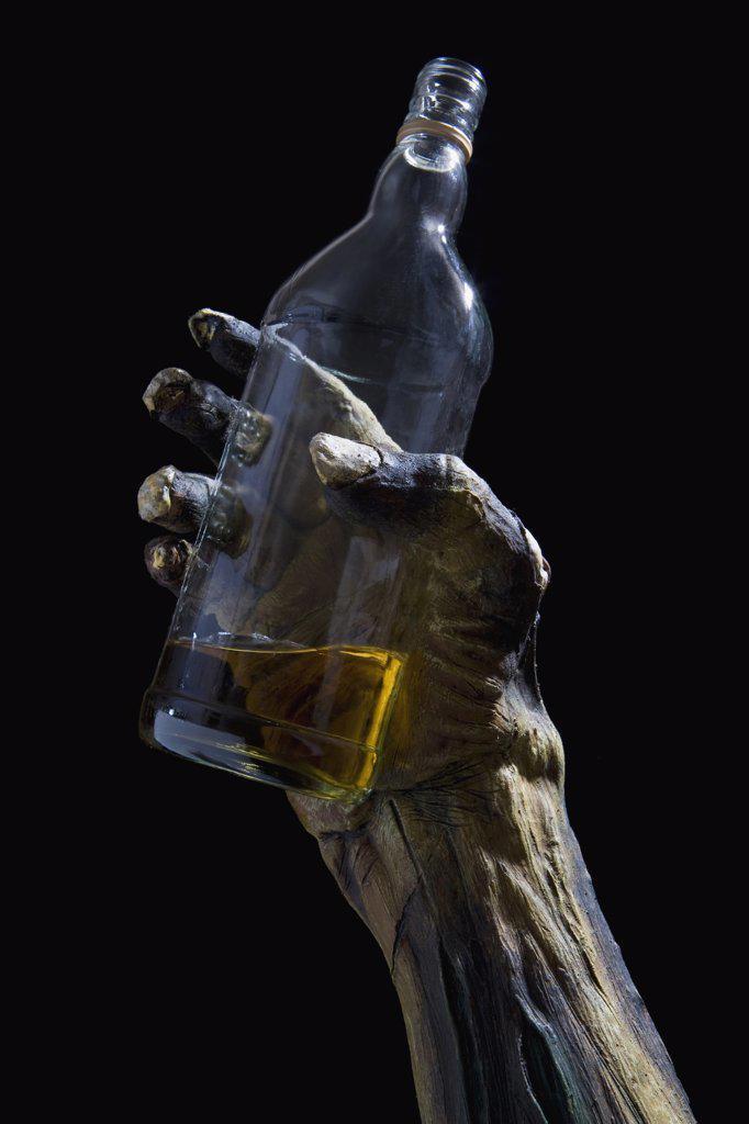 Stock Photo: 1570R-126771 Monster's hand holding a bottle