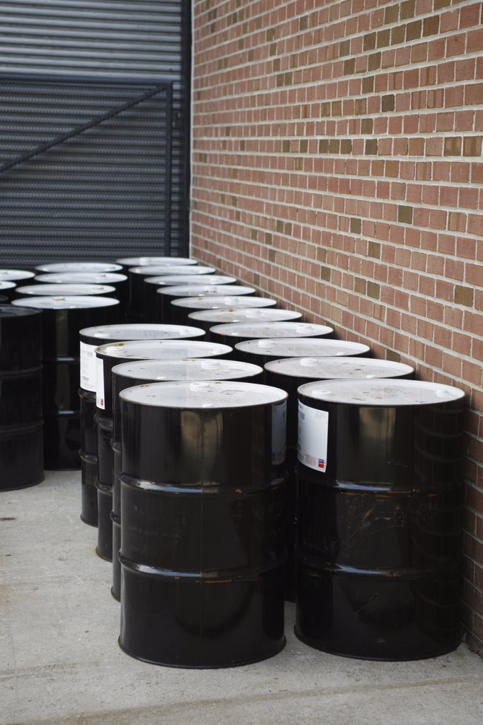 Stock Photo: 1570R-126852 Black oil drums stacked outside a building