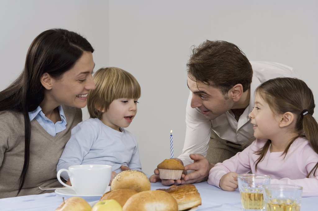 A family celebrating a the birthday of their son : Stock Photo
