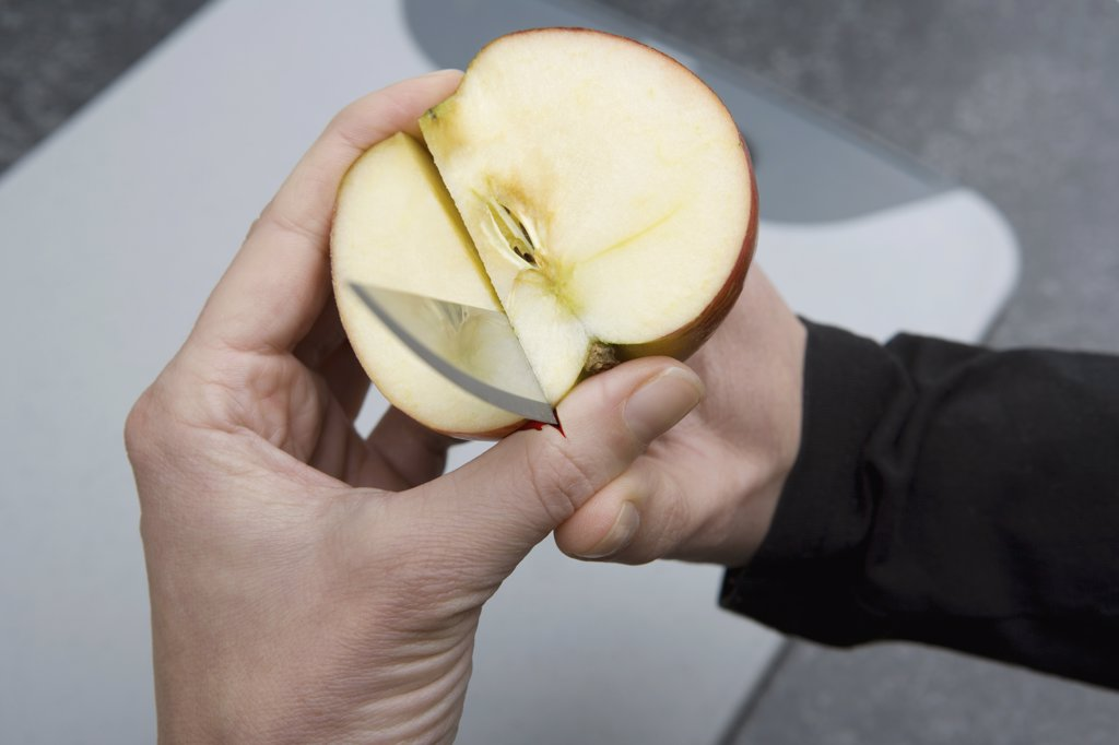 A person cutting through an apple and into their thumb : Stock Photo