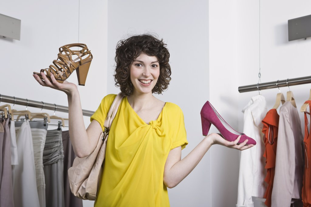 A young woman holding two shoes in a store : Stock Photo