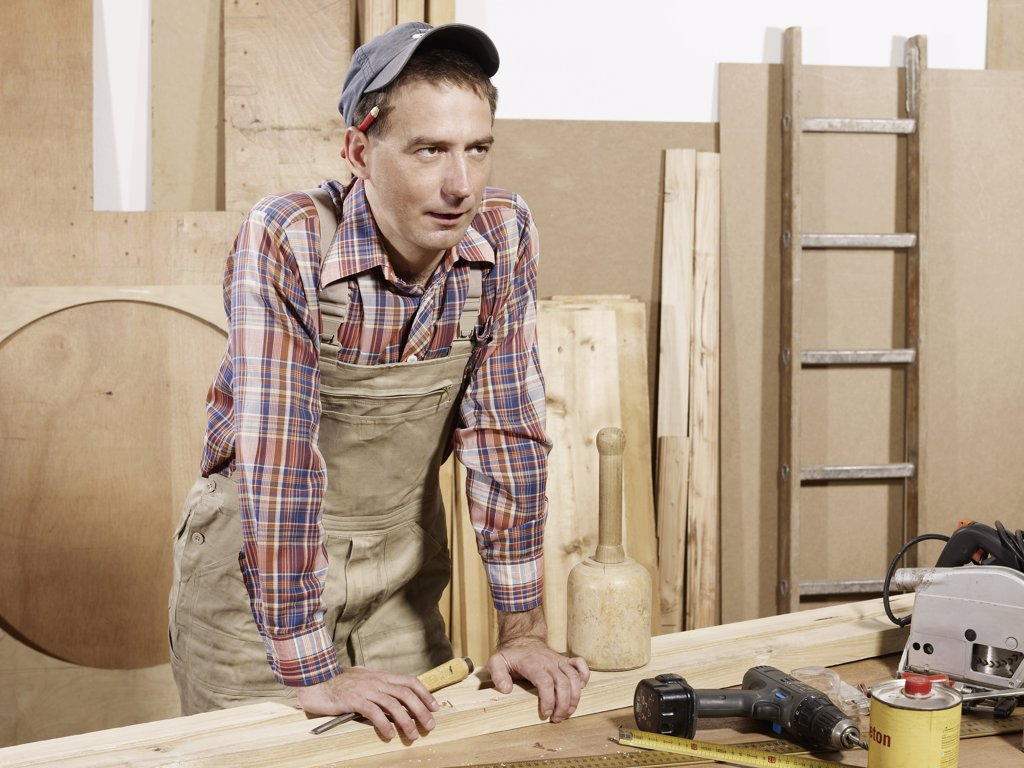 A man standing in a wood workshop : Stock Photo