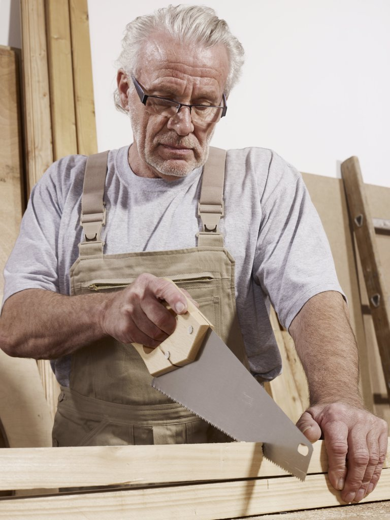 A man sawing wood : Stock Photo