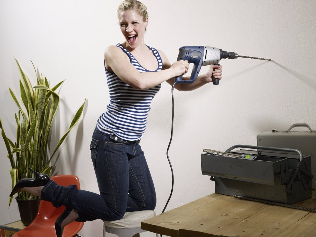 A woman drilling into a wall : Stock Photo
